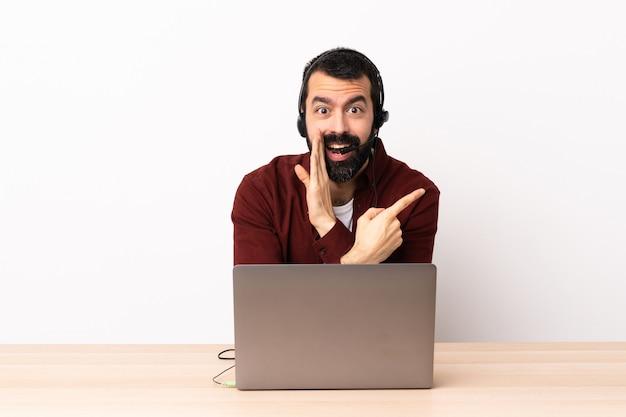 ヘッドセットと、製品を提示するために側面を指し、何かをささやくラップトップを操作するテレマーケティング白人男
