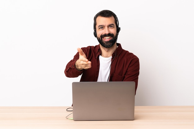 Телемаркетер кавказский человек работает с гарнитурой и с ноутбуком рукопожатие для закрытия хорошей сделки