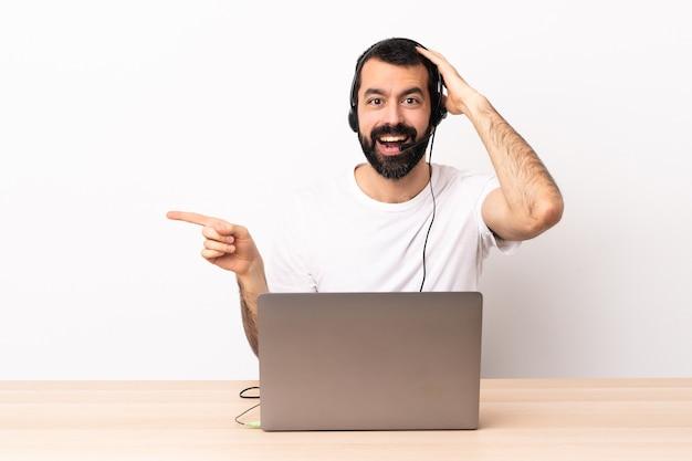 헤드셋을 사용 하 고 노트북 놀라게 하 고 측면에 손가락을 가리키는 텔레마케터 백인 남자.
