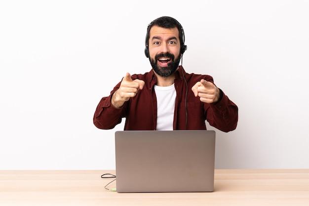 헤드셋 및 노트북 놀라게 하 고 앞을 가리키는 텔레마케터 백인 남자.