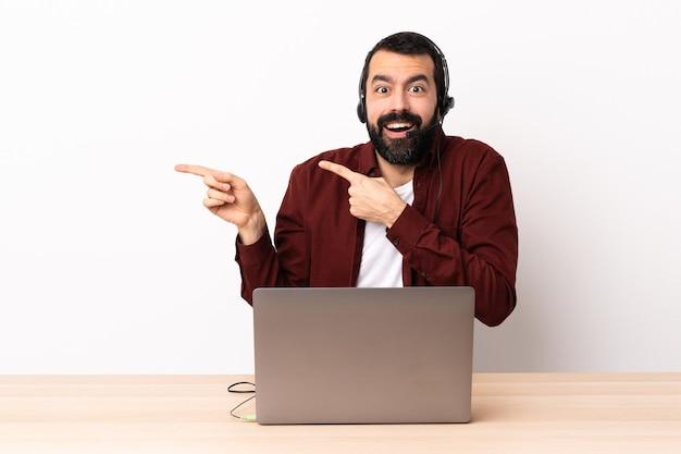 헤드셋을 사용 하 고 노트북을 놀라게 하 고 측면을 가리키는 텔레마케터 백인 남자.