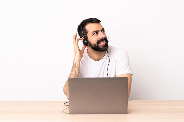 헤드셋을 사용 하 고 아이디어를 생각하는 노트북을 사용하는 텔레마케터 백인 남자.