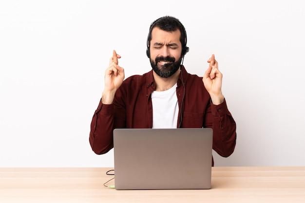 Телемаркетер кавказский человек, работающий с гарнитурой и с ноутбуком с скрестив пальцы