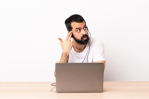 Кавказский человек телемаркетинга работает с гарнитурой и с ноутбуком с проблемами, делая жест самоубийства.