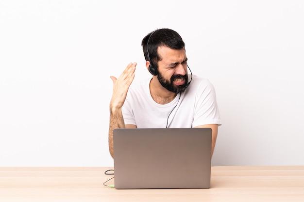 Телемаркетер кавказских человек, работающий с гарнитурой и с ноутбуком с усталым и больным выражением.
