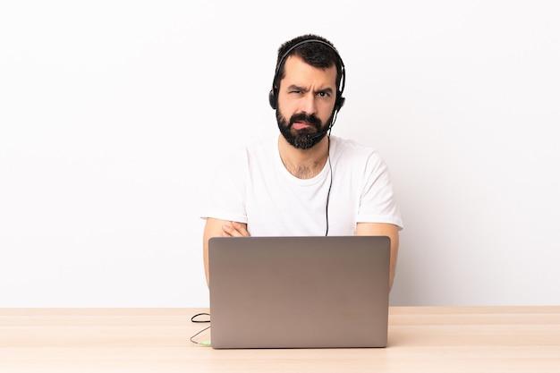 Кавказский человек телемаркетинга, работающий с гарнитурой и ноутбуком с несчастным выражением лица.
