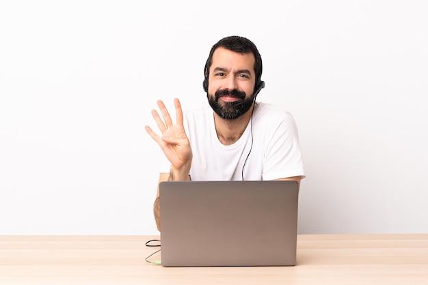 Телемаркетер кавказский человек, работающий с гарнитурой и с ноутбуком