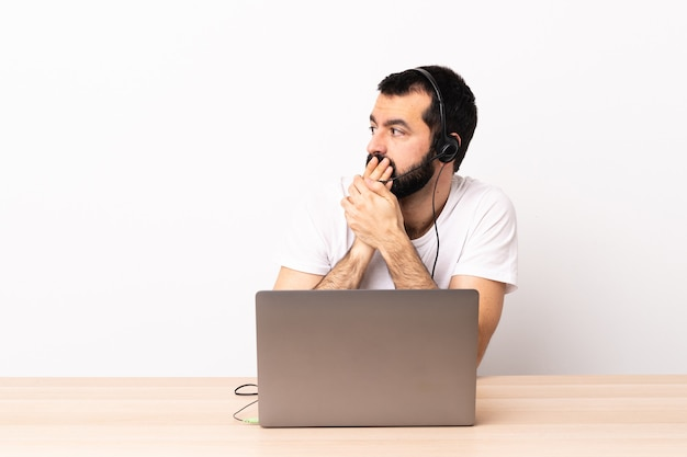 Telemarketer caucasian man working with a headset and with laptop covering mouth and looking to the side.