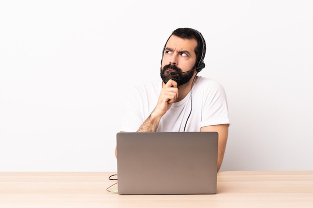 Telemarketer caucasian man working with a headset and with laptop having doubts and thinking.