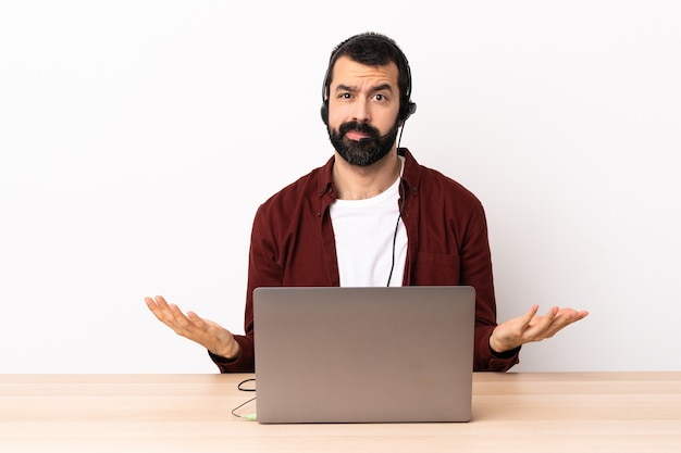 Telemarketer caucasian man working with a headset and with laptop having doubts.