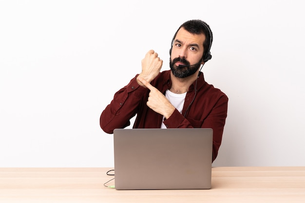 Telemarketer caucasian man working with a headset and with laptop making the gesture of being late.