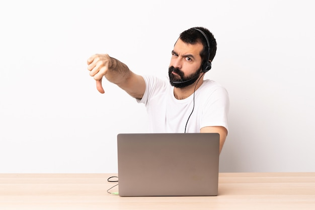 Telemarketer caucasian man working with a headset and with laptop showing thumb down with negative expression