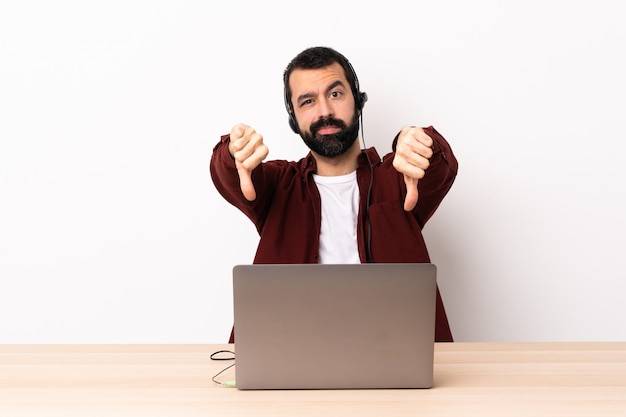 Telemarketer caucasian man working with a headset and with laptop showing thumb down with two hands