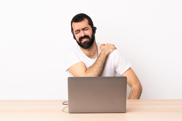 Telemarketer caucasian man working with a headset and with laptop suffering from pain in shoulder for having made an effort