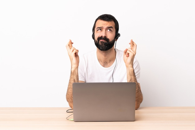 Telemarketer caucasian man working with a headset and with laptop with fingers crossing and wishing the best.