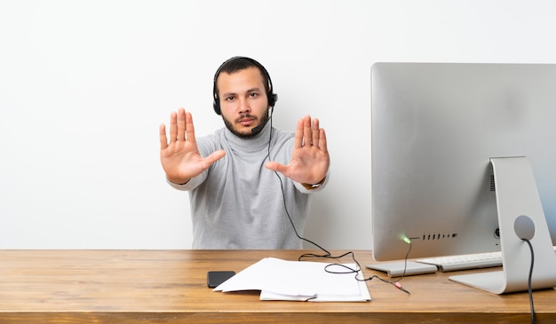 Telemarketer colombian man making stop gesture and disappointed