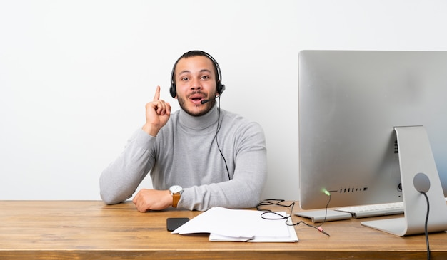 Telemarketer colombian man thinking an idea pointing the finger up