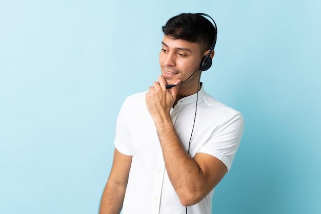 テレマーケティングのコロンビア人男性がヘッドセットを操作して、横を向いて笑顔で孤立している