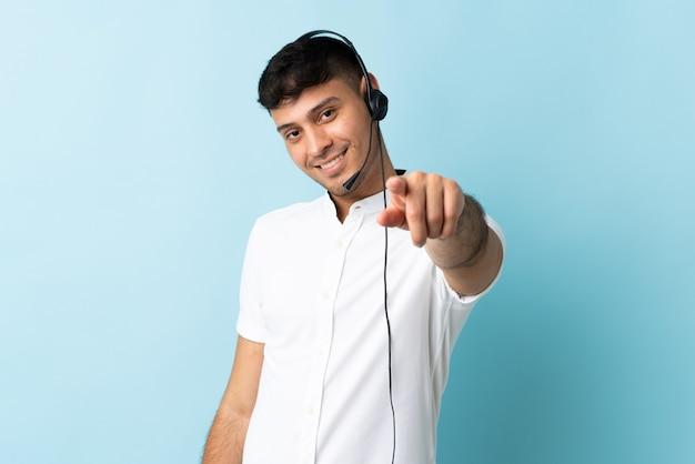 幸せな表情で孤立したポインティングフロント上でヘッドセットを使用して作業しているテレマーケティングコロンビア人