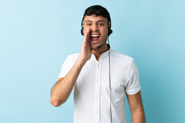 口を大きく開いて孤立した叫び声でヘッドセットを使用して作業しているテレマーケティングコロンビア人