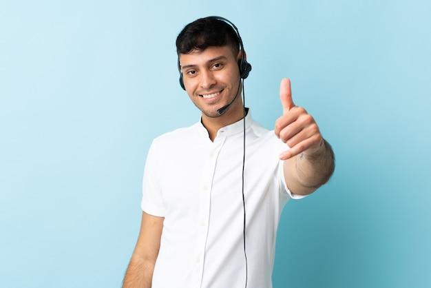 何か良いことが起こったので、親指を立てて隔離されたヘッドセットで作業しているテレマーケティングのコロンビア人男性