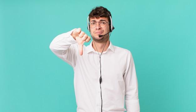 テレマーケティング担当者は、真剣な表情で親指を下に向けて、交差、怒り、イライラ、失望、または不満を感じています
