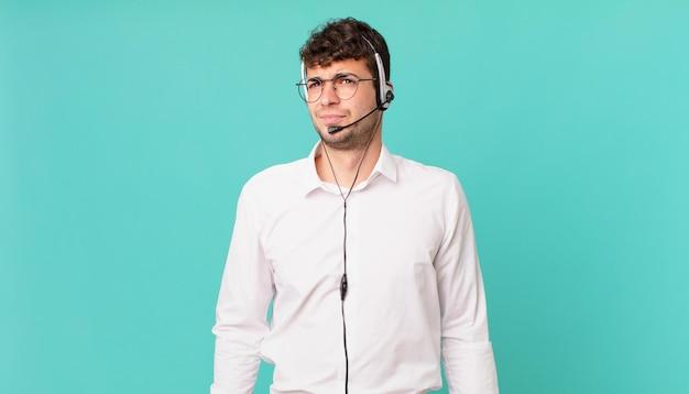 テレマーケティング担当者は、悲しみ、動揺、または怒りを感じ、否定的な態度で横を向いて、意見の相違に眉をひそめます