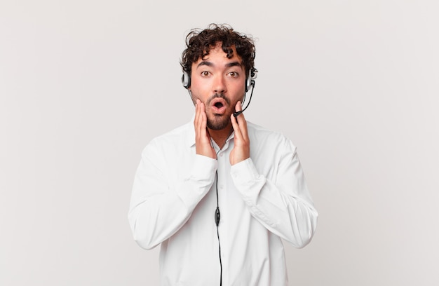 Telemarketer feeling shocked and scared, looking terrified with open mouth and hands on cheeks