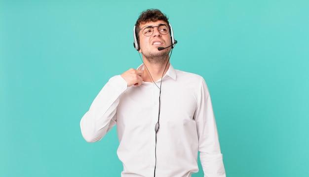 Телемаркетолог чувствует стресс, тревогу, усталость и разочарование, тянет рубашку за шею, выглядит разочарованным из-за проблемы