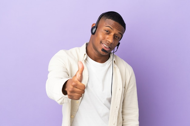 Telemarketer latin man working with a headset isolated on purple wall with thumbs up because something good has happened