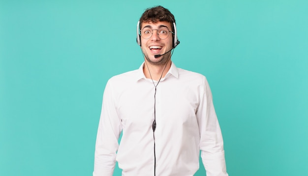 Telemarketer looking happy and pleasantly surprised, excited with a fascinated and shocked expression