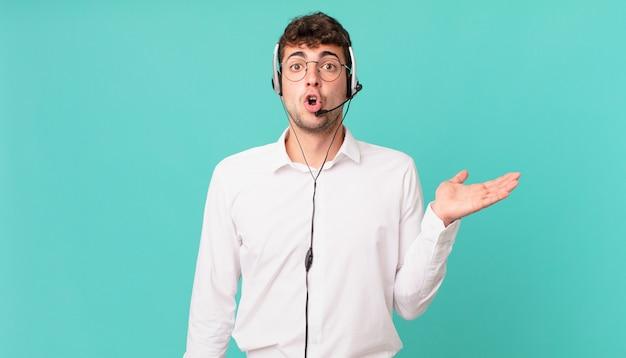 驚いてショックを受けたテレマーケティング担当者は、横に開いた手でオブジェクトを持って顎を落としました