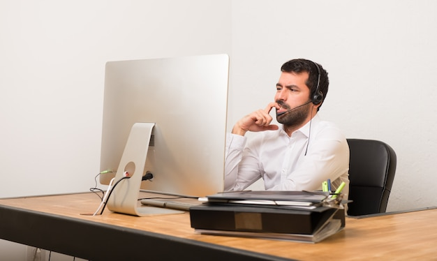 Telemarketer man in a office having doubts while looking up