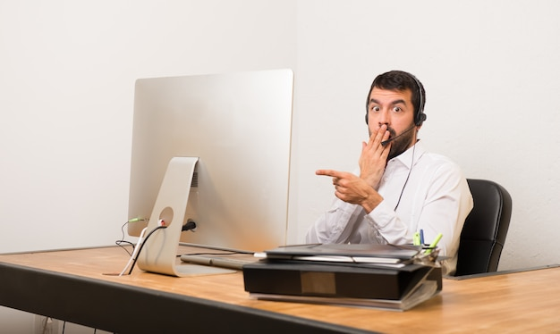 Telemarketer man in a office pointing finger to the side with a surprised face