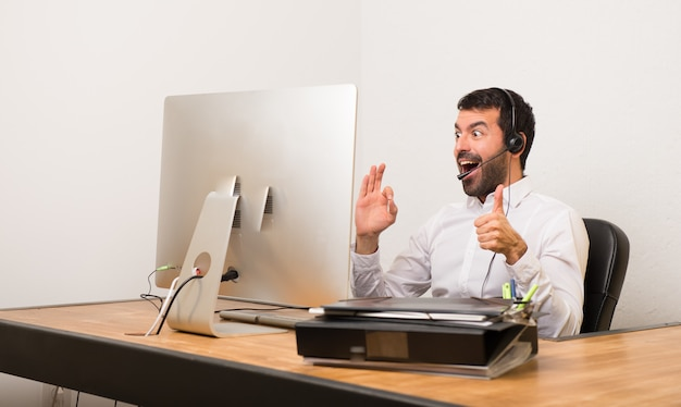 Telemarketer man in a office showing ok sign with and giving a thumb up gesture