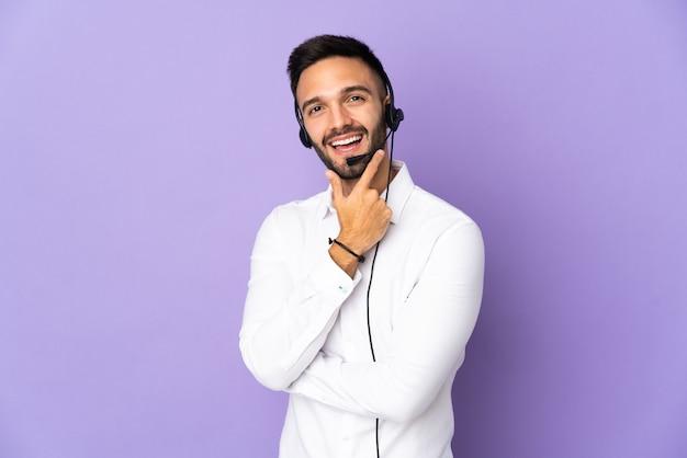 행복하고 웃는 보라색 배경에 고립 헤드셋 작업 텔레마케터 남자