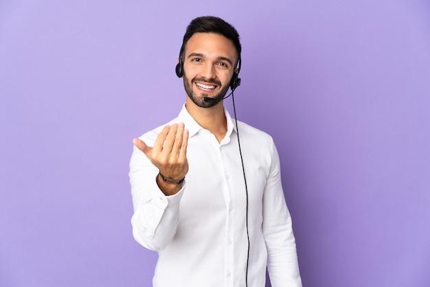 手で来るように誘う紫色の背景に分離されたヘッドセットで作業しているテレマーケティングの男。あなたが来て幸せ