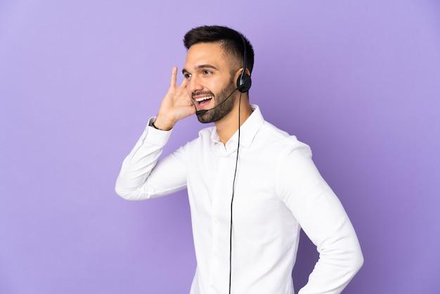 귀에 손을 넣어 뭔가를 듣고 보라색 배경에 고립 된 헤드셋 작업 텔레마케터 남자