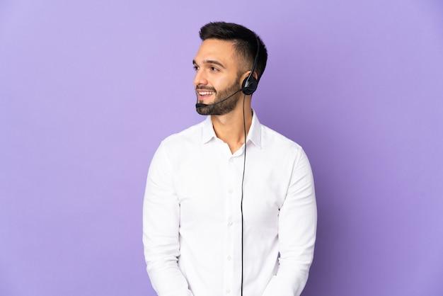 Человек-телемаркетер, работающий с гарнитурой на фиолетовом фоне, смотрит в сторону и улыбается