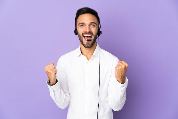 勝者の位置での勝利を祝う紫色の壁に分離されたヘッドセットで作業するテレマーケティングの男