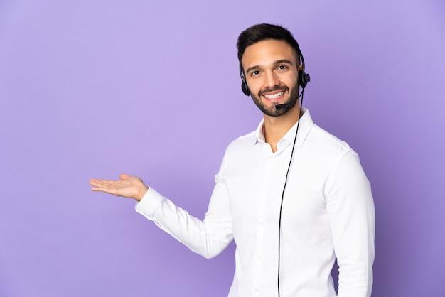 Мужчина-телемаркетер, работающий с гарнитурой, изолирован на фиолетовой стене, протягивает руки в сторону, приглашая прийти