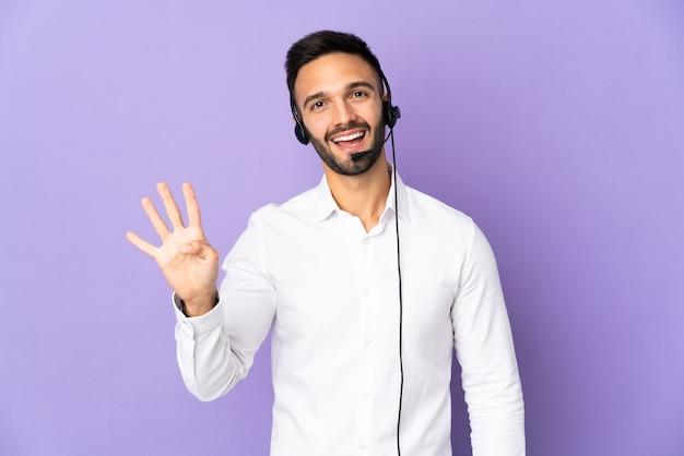 Человек-телемаркетер, работающий с гарнитурой, изолированный на фиолетовой стене, счастлив и считает четыре пальцами