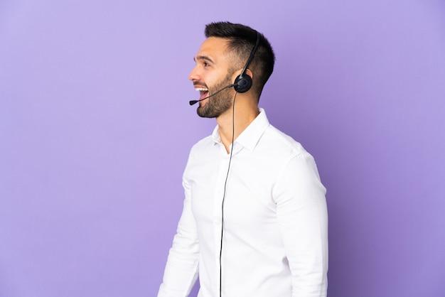 横の位置で笑っている紫色の壁に分離されたヘッドセットで作業しているテレマーケティングの男