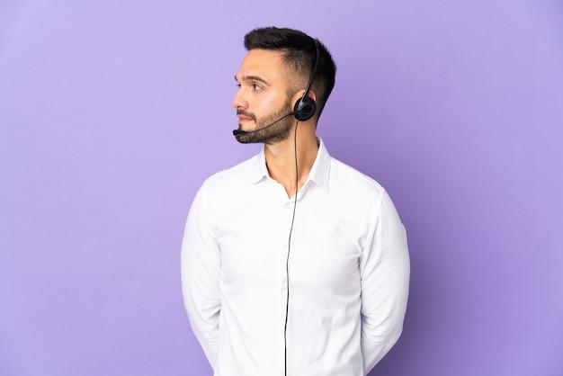 Человек-телемаркетер, работающий с гарнитурой, изолирован на фиолетовой стене, глядя в сторону