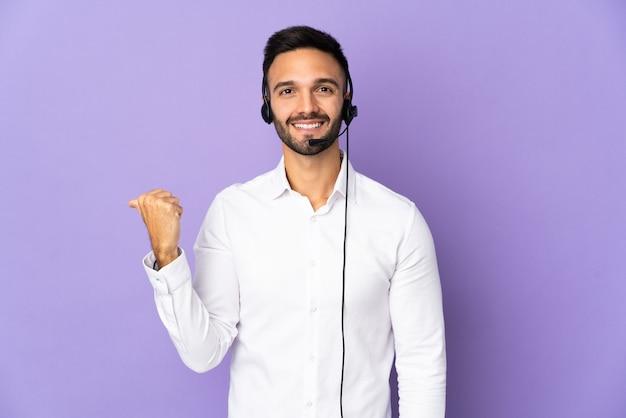 Человек-телемаркетер, работающий с гарнитурой, изолирован на фиолетовой стене, указывая в сторону, чтобы представить продукт