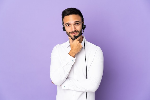紫色の壁の思考に分離されたヘッドセットで作業するテレマーケティングの男