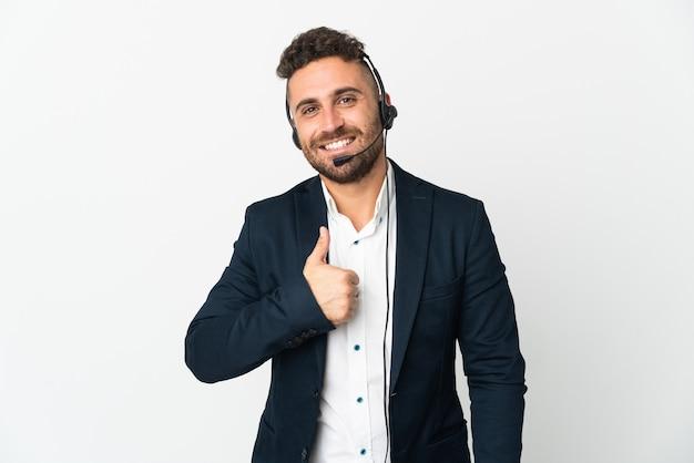 親指を立てるジェスチャーを与える白い背景で隔離のヘッドセットで作業するテレマーケティングの男