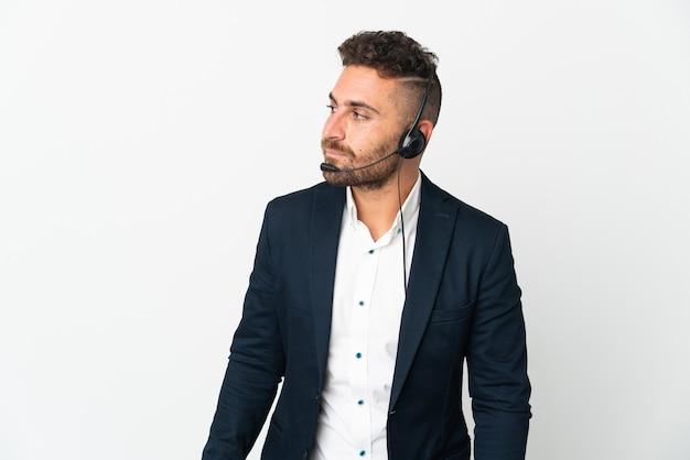 Человек-телемаркетер, работающий с гарнитурой на белом фоне, глядя в сторону