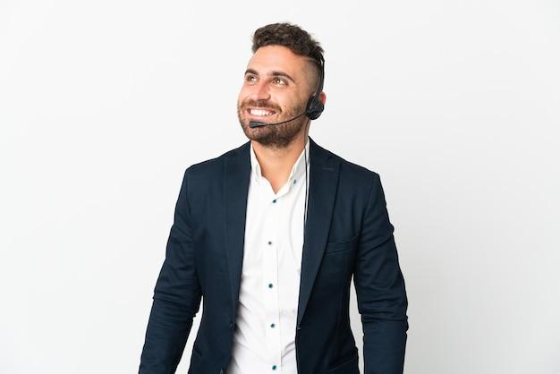 Человек телемаркетинга, работающий с гарнитурой, изолирован на белом фоне, думая об идее, глядя вверх