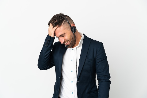 흰 벽 웃음에 고립 된 헤드셋 작업 텔레마케터 남자